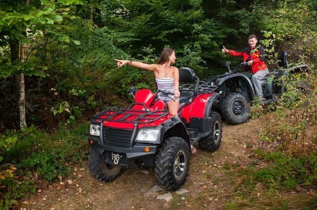 Hermosa pareja conduciendo un atv de cuatro ruedas y mirándose.