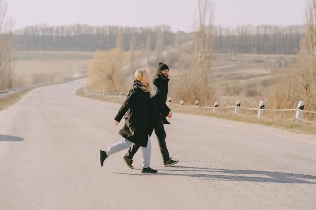 Hermosa pareja cruzando una carretera