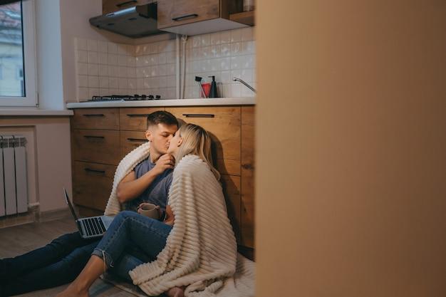 Hermosa pareja cubierta con una colcha se besan en la cocina en el piso