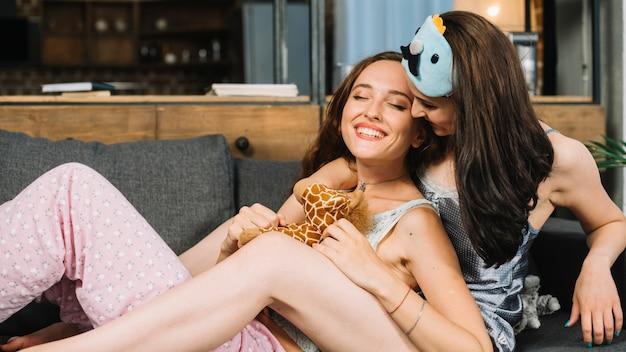 Hermosa pareja de lesbianas apoyándose en el sofá