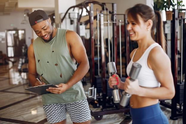 Una hermosa pareja de deportes se dedica a un gimnasio.