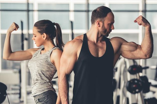 Hermosa pareja deportiva está mostrando sus músculos.