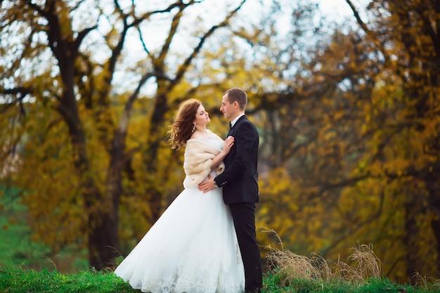 Hermosa pareja disfrutando el abrazo el uno del otro y tiernamente sonriendo
