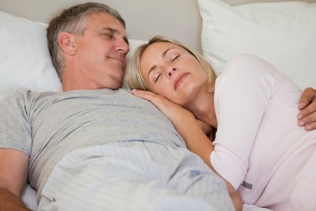 Hermosa pareja durmiendo en su cama