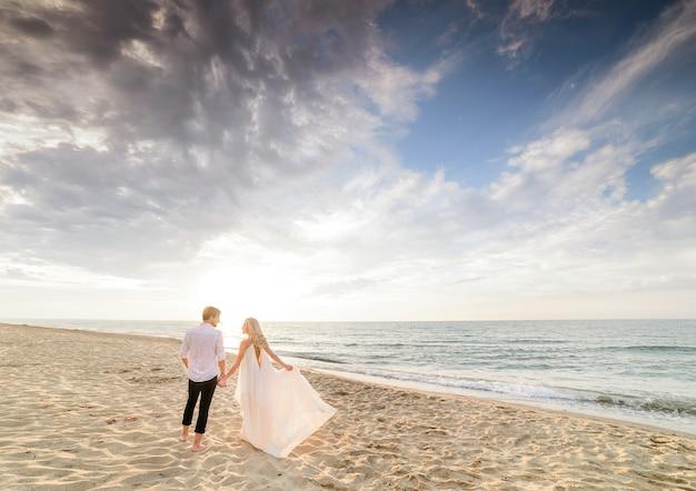 Hermosa pareja elegante caminando en la playa