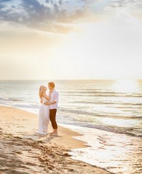 Hermosa pareja elegante posando en la luz del sol en la playa