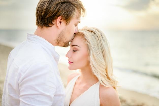 Hermosa pareja elegante posando en la playa