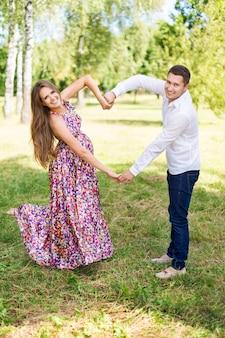 Hermosa pareja embarazada feliz juntos esperando un hijo. hombre y mujer caminando en el parque que muestra el corazón con las manos. comparte el amor y la familia, el concepto de amor.
