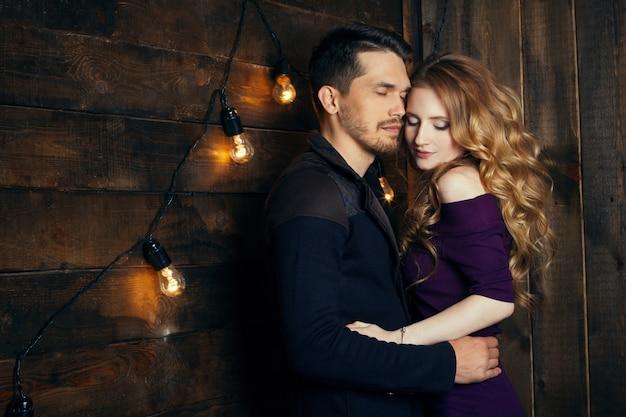 Hermosa pareja de enamorados abrazándose contra luces