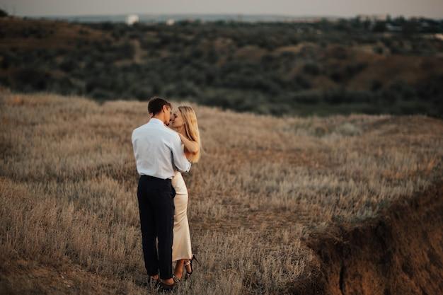 Hermosa pareja de enamorados abrazándose con los ojos cerrados. feliz chica rubia susurrando sobre el amor.