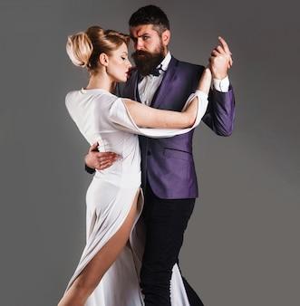 Hermosa pareja de enamorados bailando tango con pasión. bailarines profesionales en salón de baile.