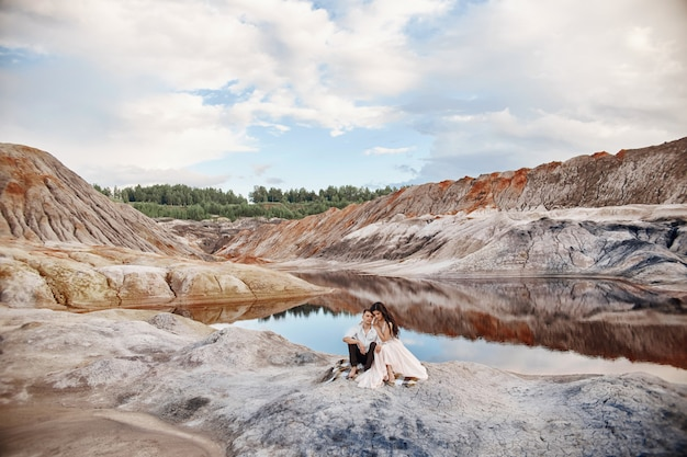 Hermosa pareja de enamorados besándose y abrazándose sentado en las rocas