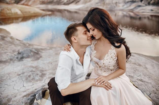 Hermosa pareja de enamorados besándose abrazándose sentado