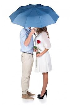 Hermosa pareja de enamorados besándose bajo el paraguas.