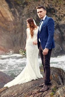 Hermosa pareja de enamorados besándose de pie en las rocas