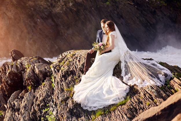 Hermosa pareja de enamorados besándose sentada en las rocas
