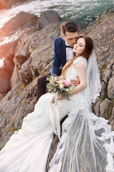 Hermosa pareja de enamorados besándose sentado en las rocas