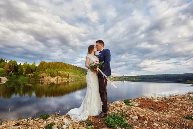 Hermosa pareja de enamorados besándose en el suelo junto al lago