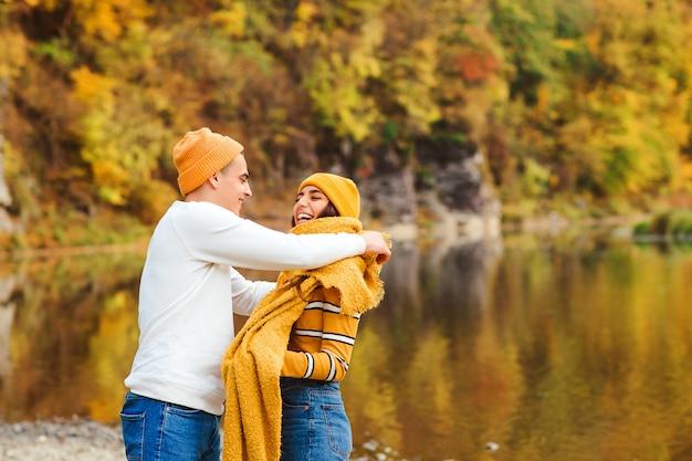 Hermosa pareja de enamorados caminando en el parque otoño. feliz pareja joven divirtiéndose juntos al aire libre. amor, relación y concepto de moda.