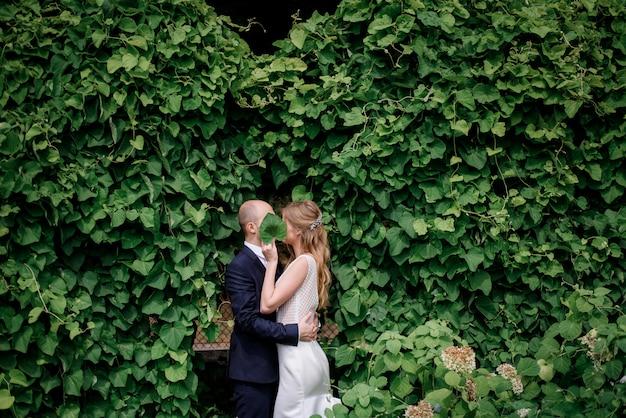 Hermosa pareja de enamorados cerca de la pared cubierta de hiedra verde, cubriendo caras con hojas