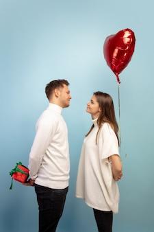 Hermosa pareja de enamorados con globo en forma de corazón en la pared azul del estudio