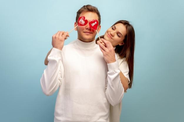 Hermosa pareja de enamorados en la pared azul del estudio