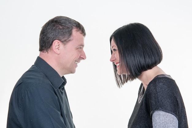 Hermosa pareja feliz amor sonriendo el uno al otro, hombre y mujer sonríen aislado en blanco
