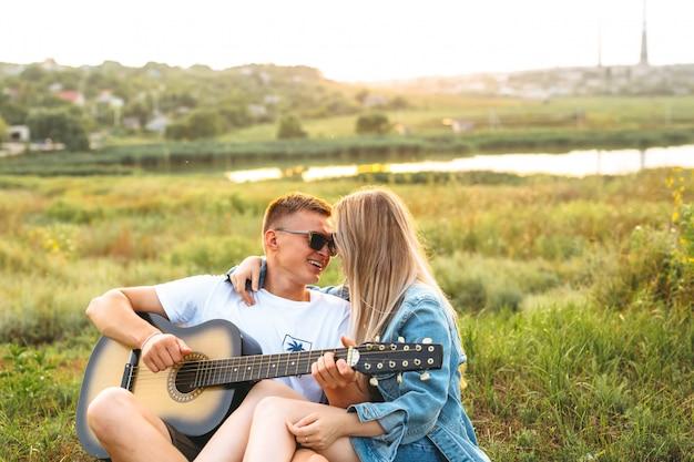 Una hermosa pareja feliz enamorada de gafas de sol tocando la guitarra y regocijándose al atardecer