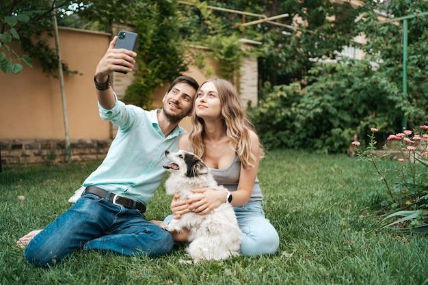 Hermosa pareja feliz haciendo selfie con su adorable perro en el patio trasero mientras está sentado en el césped