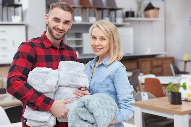 Hermosa pareja feliz sonriendo a la cámara, comprando acogedoras mantas suaves en la tienda de artículos para el hogar
