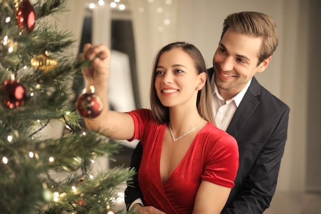 Hermosa pareja haciendo el árbol de navidad en casa
