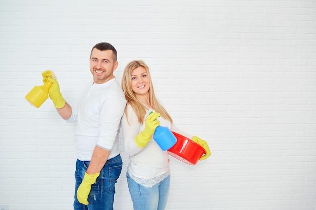 Hermosa pareja haciendo limpieza sobre fondo blanco.