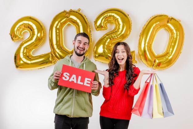 Hermosa pareja hombre y mujer con cartel de venta y coloridos bolsos de compras frente a 2020 globos
