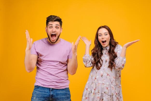 Hermosa pareja hombre y mujer sorprendida y gritando aislado