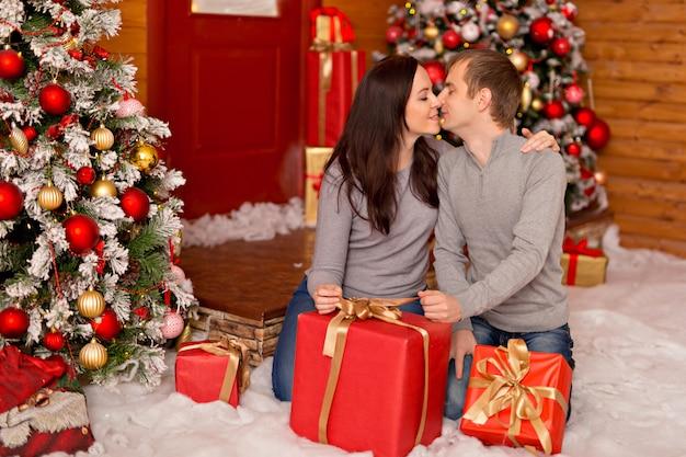 Hermosa pareja, una joven familia en anticipación de feliz navidad abre regalos.