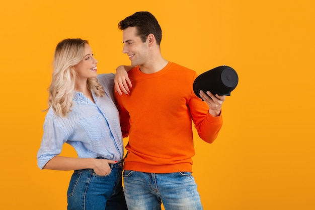 Hermosa pareja joven sonriente sosteniendo altavoz inalámbrico escuchando música en naranja