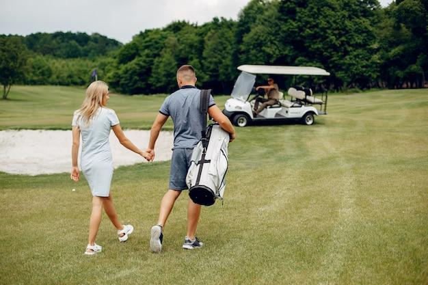 Hermosa pareja jugando al golf en un campo de golf