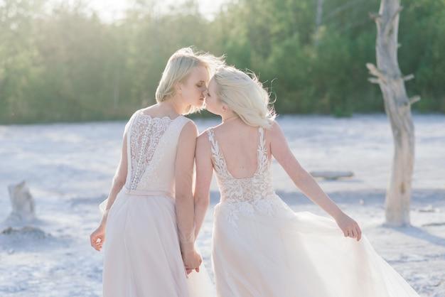 Hermosa pareja de lesbianas caminando sobre la arena a lo largo de la orilla de un río en el día de su boda