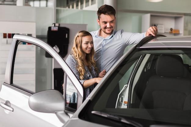 Hermosa pareja mirando un auto