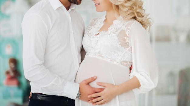 Hermosa pareja de mujer embarazada y su marido abrazando.
