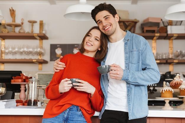 Hermosa pareja mujer y hombre en ropa casual sonriendo y tomando café en la panadería