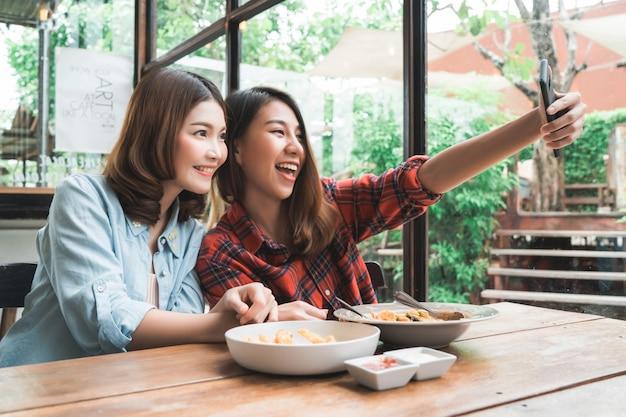 Hermosa pareja de mujeres asiáticas lesbianas lgbt sentadas a cada lado comiendo un plato de mariscos italianos