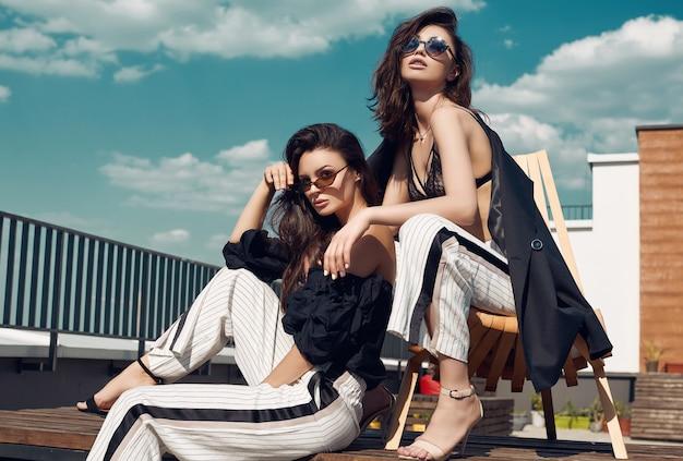 Hermosa pareja de mujeres morenas en vestidos de moda posando en el techo