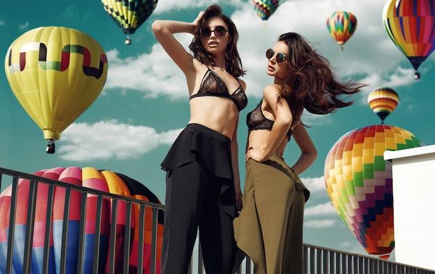 Hermosa pareja de mujeres en sujetador contra el fondo de globos aerostáticos