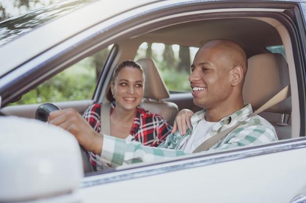 Hermosa pareja multirracial disfrutando de viajar en coche