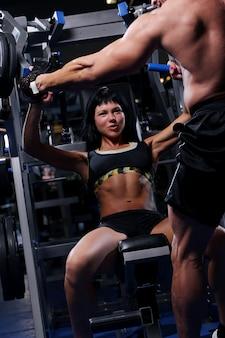 Hermosa pareja muscular en el gimnasio