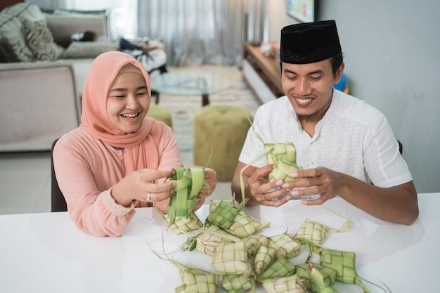 Hermosa pareja musulmana asiática haciendo pastel de arroz ketupat en casa con hoja de palma