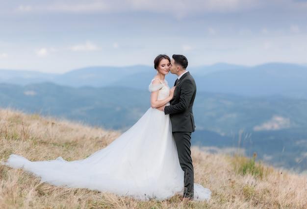 Hermosa pareja de novios se besa en la cima de una montaña en el cálido día de otoño