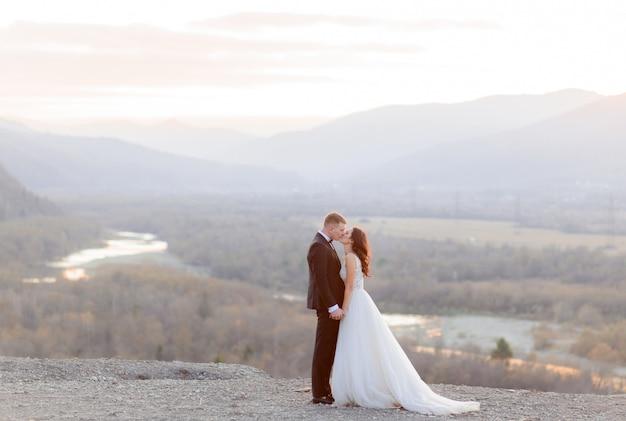 Hermosa pareja de novios se besa en la colina con vistas a un pintoresco paisaje al atardecer