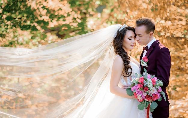 Hermosa pareja de novios en el bosque con árboles amarillentos casi besándose, concepto de matrimonio, novios en el bosque de otoño